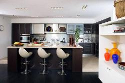 Modular Kitchen with stainless steel Appliances and Laminates on cabinets and wooden Kitchen Island and modern barstools