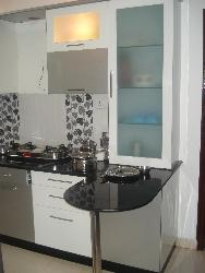 Black colored granite on L shaped Kitchen counter top with white colored cabinets