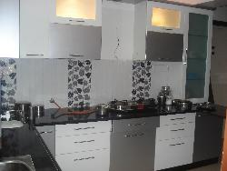 Black colored granite on Kitchen counter top with white colored cabinets