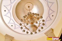 Ornamental chandelier with plaster of Paris design on cove ceiling