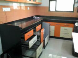 Kitchen cupboards done with twin colored laminates and using modular accessories