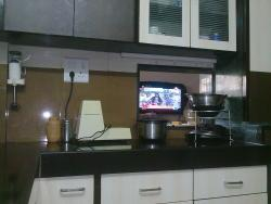 A small window connecting Kitchen and Living room so that TV is visible in Kitchen