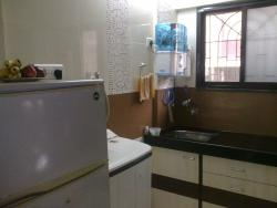 A corner with a washing machine and a Sink with storage around the place