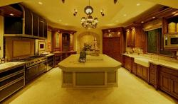 Warm yellow lights, marble flooring in a large kitchen with island