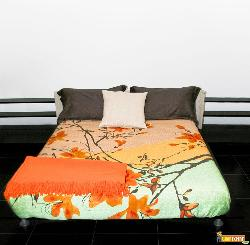 Bedroom with big double bed and colorful sheets