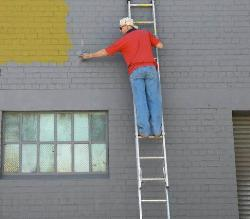 Person doing paint on exterior wall