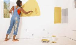 A girl doing paint on a interior wall