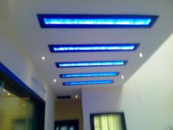 Ceiling design for a Lobby area with blue cove lights covered with glass