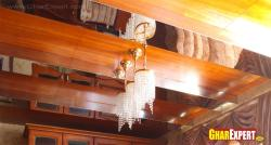 Small chandelier hanged on striped wood and mirror ceiling