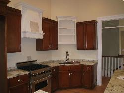 Wooden kitchen having stainless steel cooking range and wooden cover for hood