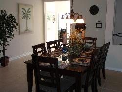 8 seater dining table with rough tile flooring and chandelier over the table