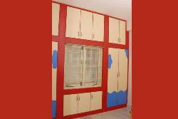 Red color wardrobes in bedroom with window in  it.