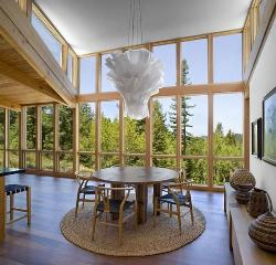 Double height living room with large windows wooden flooring, modern chandelier